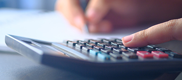 Individual using calculator to tally medical bills