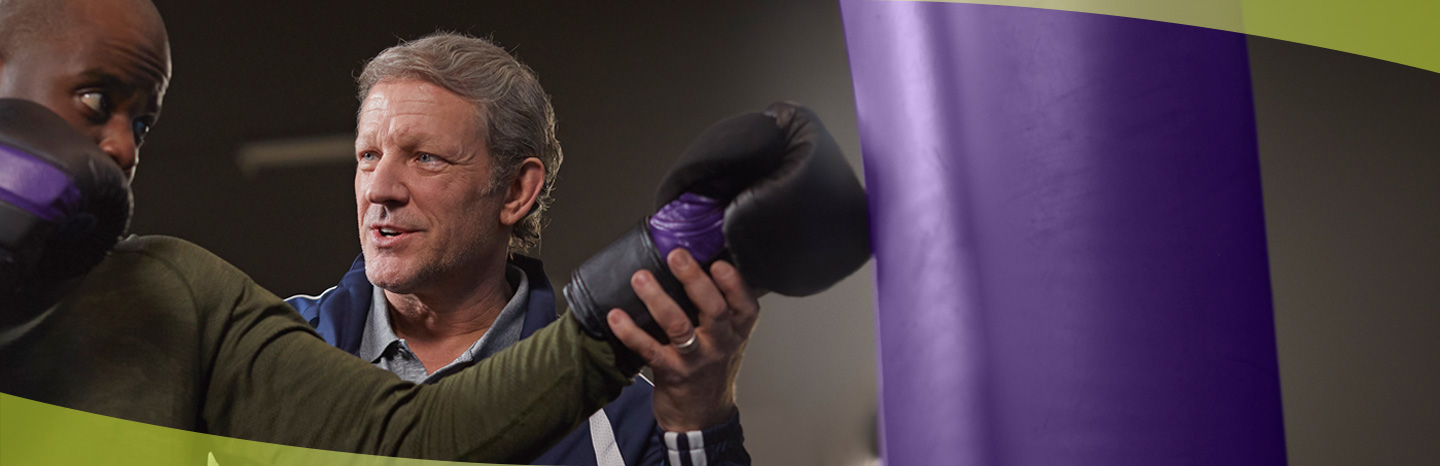 Boxing coach with prostate cancer from ERLEADA® (apalutamide) commercial teaching the ring